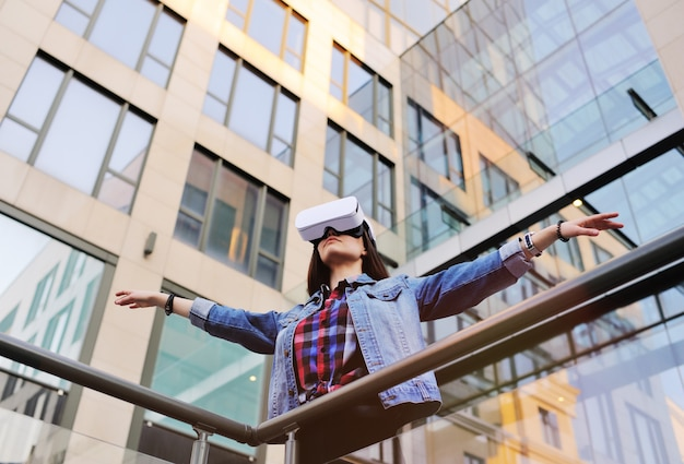Junge frau mit dem langen haar in vr-gläsern auf modernem glasgebäude