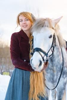 Junge frau mit dem langen haar mit pferd im winter