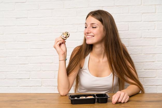 Junge frau mit dem langen haar sushi essend