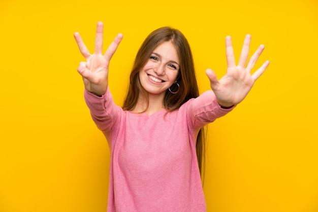 Junge frau mit dem langen haar über der lokalisierten gelben wand, die acht mit den fingern zählt