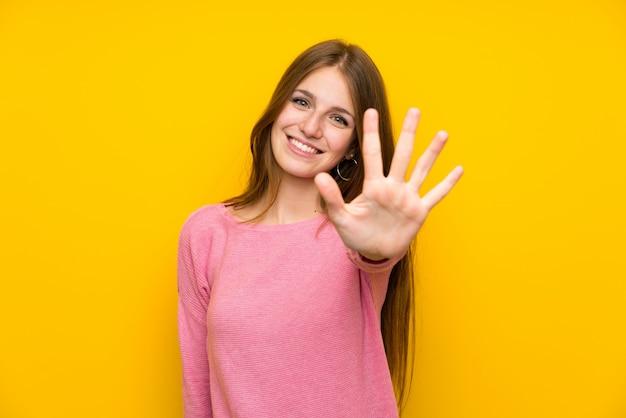 Junge frau mit dem langen haar über der lokalisierten gelben wand, die fünf mit den fingern zählt