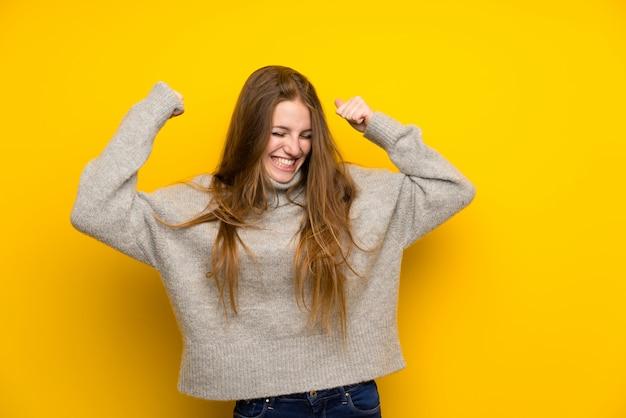 Junge frau mit dem langen haar über gelb einen sieg feiernd