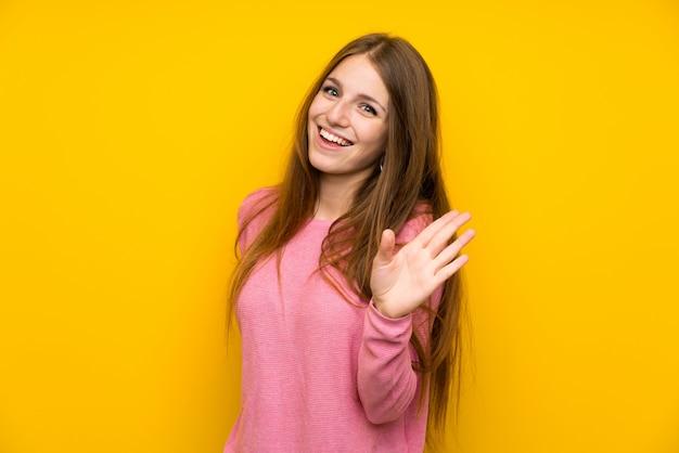 Junge frau mit dem langen haar über lokalisierter gelber wand, die mit der hand mit glücklichem ausdruck begrüßt