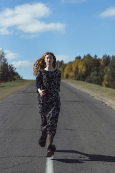 Junge frau mit dem langen roten haar in einem leinenkleid in einem natürlichen standort auf dem hintergrund