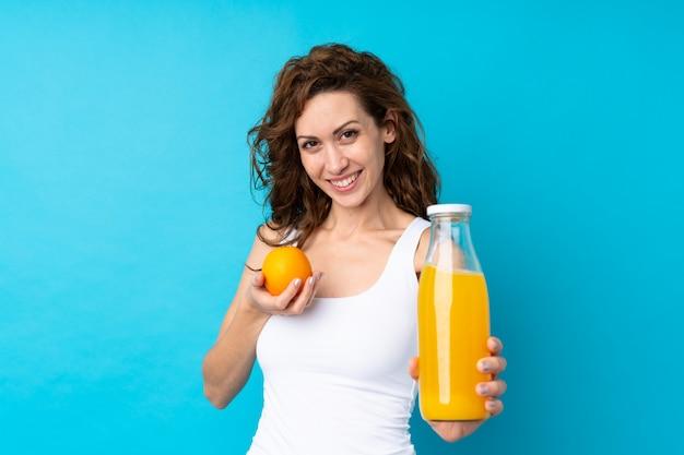 Junge frau mit dem lockigen haar, das eine orange über getrenntem blau anhält