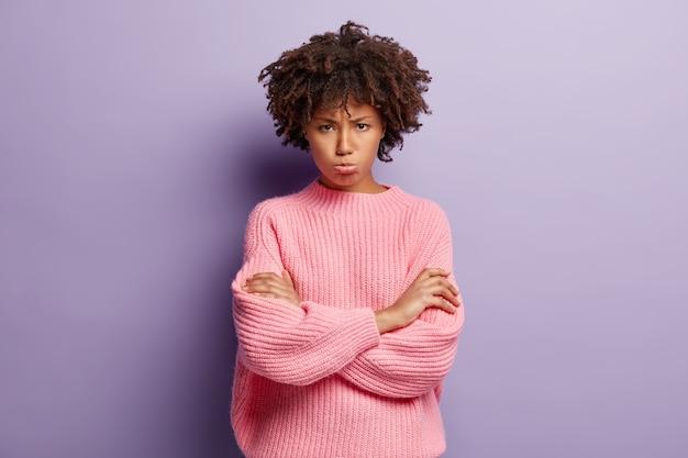 Junge frau mit dem lockigen haar, das rosa pullover trägt