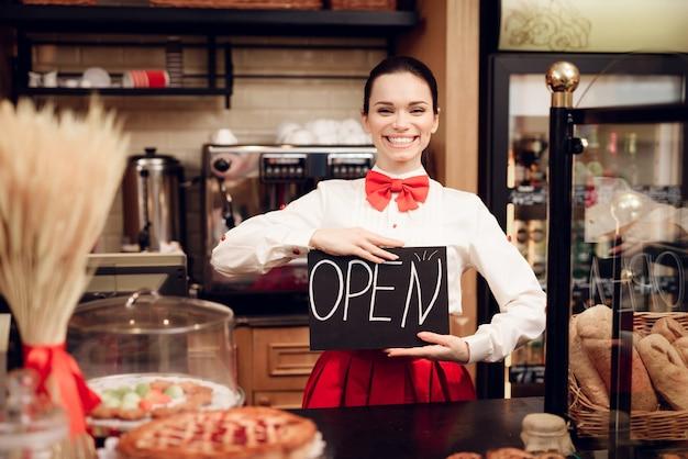 Junge frau mit dem offenen zeichen, das in der bäckerei steht.