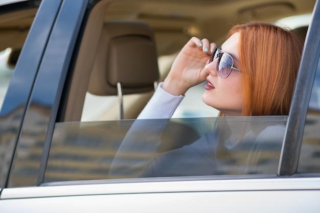Junge frau mit dem roten haar und den sonnenbrillen, die mit dem auto reisen. passagier, der aus dem hinteren fenster eines taxis in einer stadt heraus schaut.