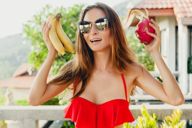 Junge frau mit dem schönen schlanken körper, der mit tropischen früchten aufwirft, die roten badeanzug des bikinis auf tropischem villenresort im urlaub in asien tragen, dünne figur, sommerarttrend, gesunde lebensstildiät