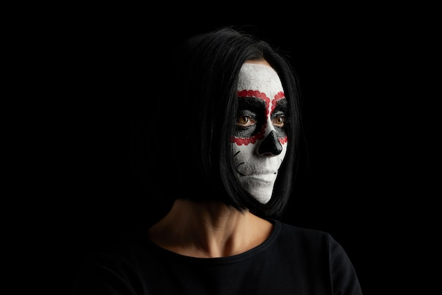 Junge frau mit dem schwarzen kurzen haar im weißen make-up zuckerkopf zum tag der toten