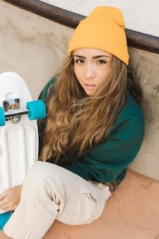 Junge frau mit dem skateboard im freien