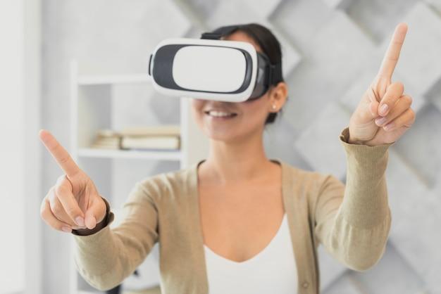 Junge frau mit dem virtuellen kopfhörerzeigen