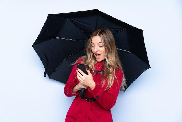 Junge frau mit dem wintermantel, der einen regenschirm und ein mobile hält