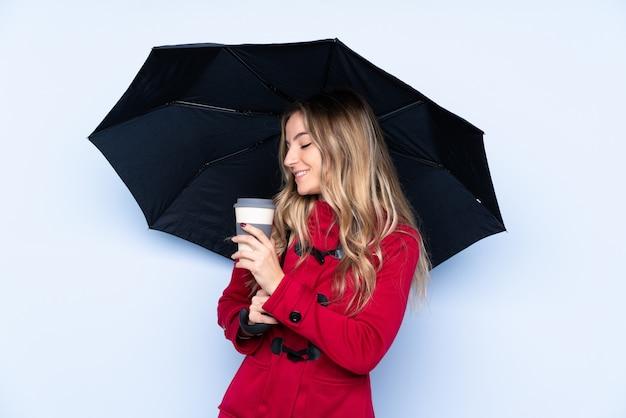 Junge frau mit dem wintermantel, der einen regenschirm und einen kaffee hält, um wegzunehmen