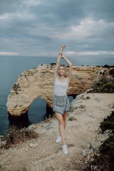 Junge frau mit den armen weit offen stehend auf felsen vor ozeanstrand auf portugal