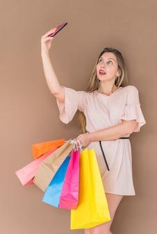 Junge Frau mit den Einkaufstaschen, die selfie nehmen