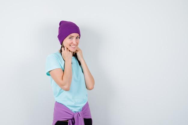 Junge frau mit den händen auf den haaren in blauem t-shirt, lila mütze und fröhlichem aussehen, vorderansicht.
