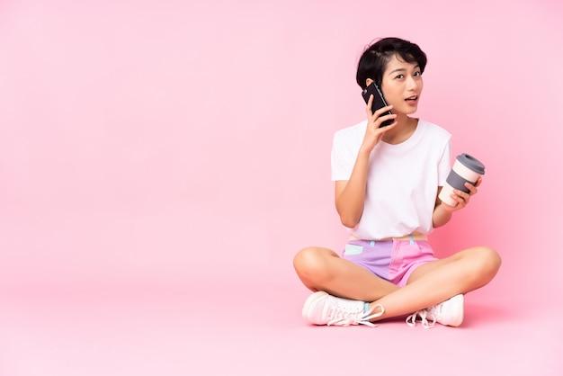 Junge frau mit den kurzen haaren, die auf dem boden über isoliertem rosa halten kaffee halten, um wegzunehmen und ein handy