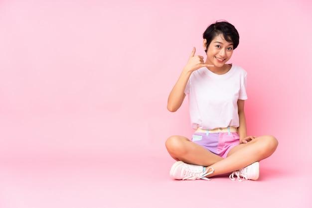 Junge frau mit den kurzen haaren, die auf dem boden über isoliertem rosa sitzen, das telefongeste macht. rufen sie mich zurück zeichen