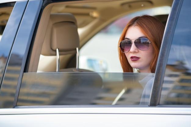 Junge frau mit den roten haaren und der sonnenbrille, die mit dem auto reisen.