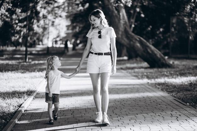 Junge frau mit der kleinen tochter, die in park geht