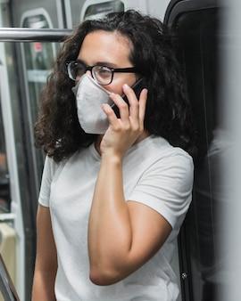 Junge frau mit der medizinischen maske, die am telefon in der u-bahn spricht