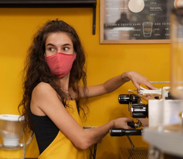 Junge frau mit der medizinischen maske, die in einem kaffeehaus arbeitet