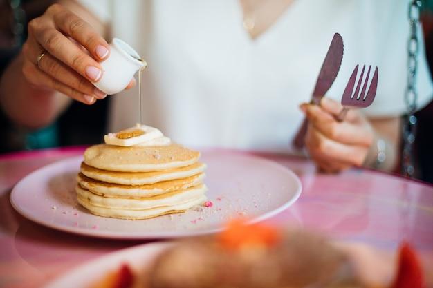Junge frau mit der rechten hand gießt honig auf portion flauschige pfannkuchen mit weichkäse und hält gabel und messer in der linken süße dessertskonzept der richtigen ernährung