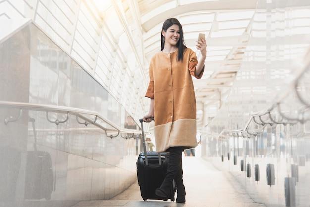 Junge frau mit der reisetasche und intelligentem telefon gehend am flughafen für reisendtourismus