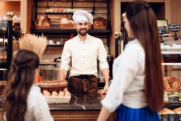 Junge frau mit der tochter, die brot in der bäckerei kauft.