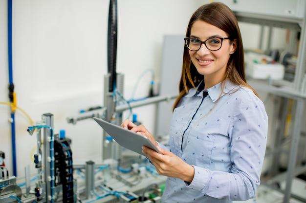 Junge frau mit digitaler tablette in der elektronikwerkstatt