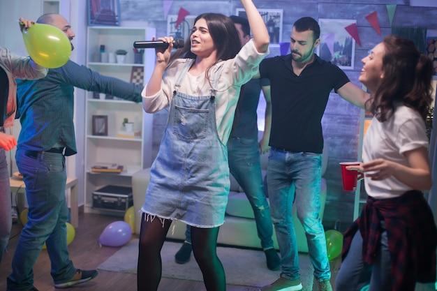 Junge frau mit dunklem haar, die auf der party für ihre freunde am mikrofon tanzt und singt.