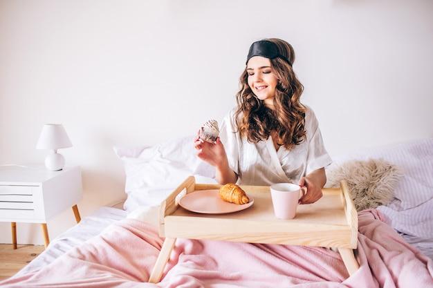 Junge frau mit dunklem haar sitzt auf bett und hält kuchen in der hand. frühstück morgen. allein im schlafzimmer. schönes modell tragen rosa pyjama und schwarze gesichtsmaske.