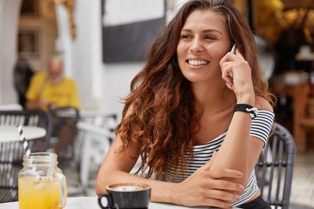 Junge frau mit dunklen langen haaren, die am telefon in einem café sprechen
