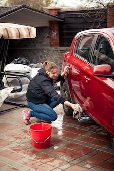 Junge frau mit eimer und lappen, die rotes auto wäscht