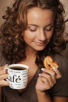 Junge frau mit einem aromatischen kaffee in den händen
