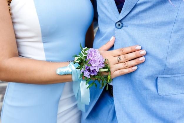 Junge frau mit einem blumenboutonniere auf einer hand in einem blauen kleid, das einen mann in einer blauen klage umarmt