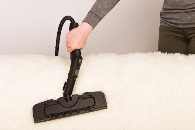 Junge frau mit einem dampfreiniger reinigt den teppich auf der couch
