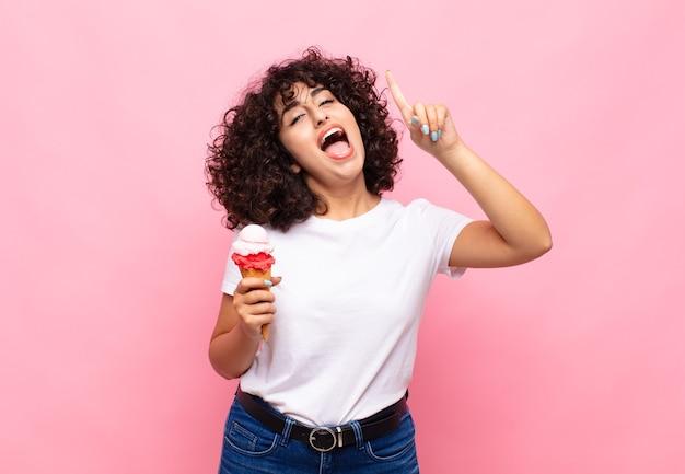 Junge frau mit einem eis, das sich wie ein glückliches und aufgeregtes genie fühlt, nachdem sie eine idee verwirklicht hat, fröhlich finger hebend, eureka!