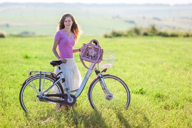 Junge frau mit einem fahrrad auf der grünen wiese an einem sonnigen tag