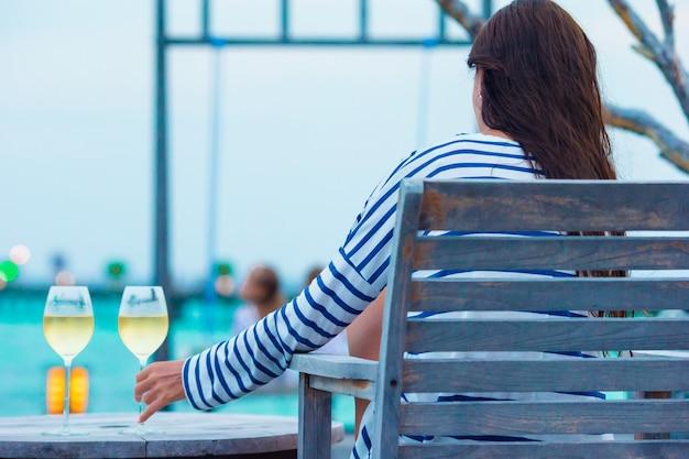 Junge frau mit einem glas weißwein am abend