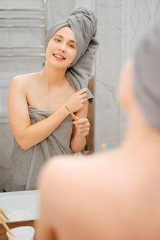 Junge frau mit einem handtuch auf dem kopf putzt sich die zähne mit einer ökobürste im badezimmer. konzept der zahnmedizin und pflege.