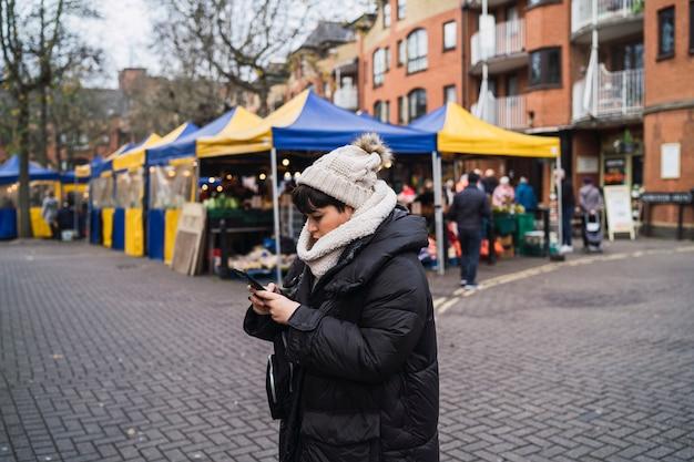 Junge frau mit einem hut und einem mantel sms auf ihrem smartphone auf der straße