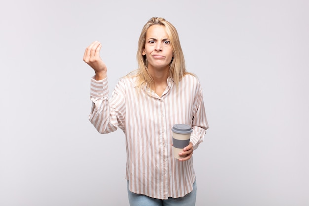 Junge frau mit einem kaffee-capice oder einer geldgeste, die ihnen sagt, sie sollen ihre schulden bezahlen!
