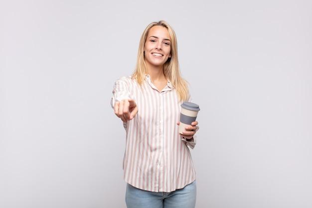 Junge frau mit einem kaffee, der mit einem zufriedenen, selbstbewussten, freundlichen lächeln auf die kamera zeigt und sie wählt