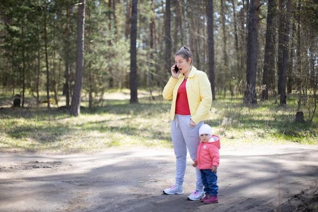 Junge frau mit einem kleinkind, die emotional in einem wald außerhalb der stadt telefoniert 4g