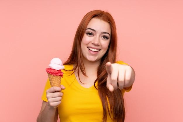 Junge frau mit einem kornetteis über isolierter wand zeigt finger auf sie mit einem selbstbewussten ausdruck