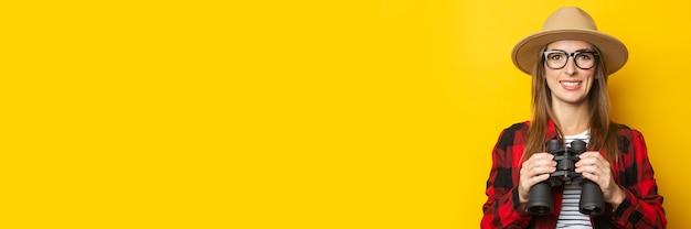 Junge frau mit einem lächeln in einem hut und einem karierten hemd, das fernglas in ihren händen auf einem gelben hintergrund hält.