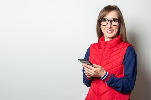 Junge frau mit einem lächeln in einer roten weste hält ihr telefon in ihren händen gegen eine helle wand