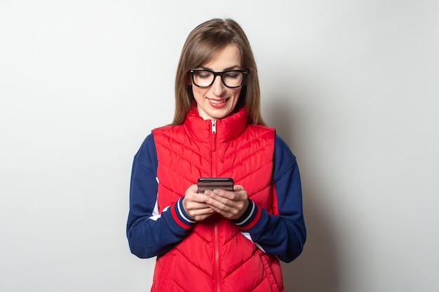 Junge frau mit einem lächeln in einer roten weste schaut in ihr telefon gegen eine helle wand